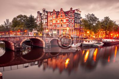Amsterdam Kanal, Brücke und typische Häuser, Boote und Fahrräder während der Abenddämmerung blaue Stunde, Holland, Niederlande. Verwendetes Tonen