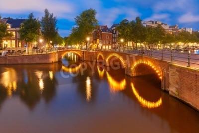 Amsterdam-Kanal, Brücke und typische Häuser, Boote und Fahrräder während der blauen Stunde der Abenddämmerung, Holland, die Niederlande.