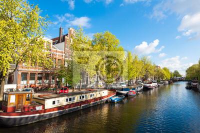 Amsterdam Kanal mit Booten entlang der Ufer des Flusses während der sonnigen Tag, Niederlande.