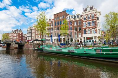 Amsterdam Kanal mit einem Hausboot am Ufer entlang, Niederlande.