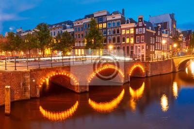 Amsterdam Kanal Reguliersgracht, Brücke und typische Häuser, Boote und Fahrräder in Abenddämmerung blaue Stunde, Holland, Niederlande.