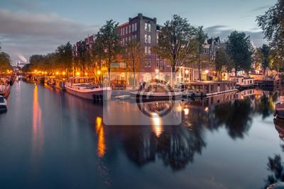 Amsterdam Kanäle und typische Häuser, Boote und Fahrräder in Abenddämmerung blaue Stunde, Holland, Niederlande.