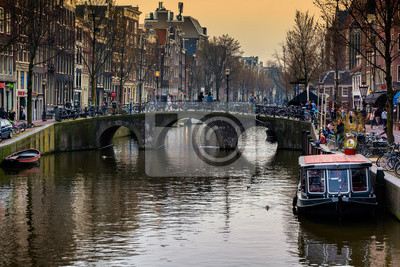 AMSTERDAM, NETHERLANDS - APRIL 10, 2018: Amsterdam canal with typical dutch houses and boats in the evening, Amsterdam, Netherlands.