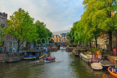 Amsterdam, Niederlande - August 3,2014: Stadtansicht des Amsterdamer Kanals mit dem Boot Ruderer im Abendlicht. Kanalring auf der UNESCO-Liste des Weltkulturerbes.