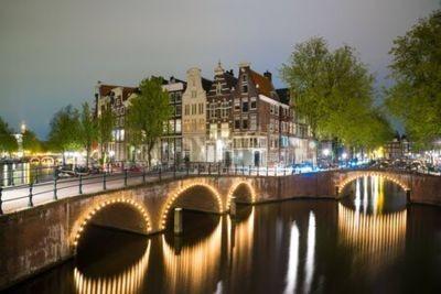 Amsterdamer Kanal, Brücke und typische Häuser während der abenddämmerungsblauen Stunde, Holland, Niederlande.