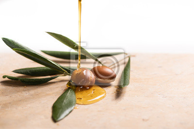 argan oil pouring over argan seeds