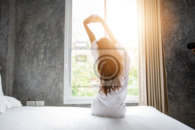 Poster Asian woman waking up in her bed fully rested and open the curtains in the morning to get fresh air.