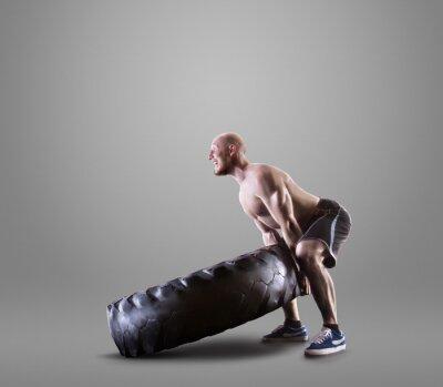 Poster Athletischer junger Mann, der einen Reifen auf grauem Studiohintergrund anhebt