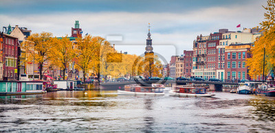 Attractive autumn scene of Amsterdam city. Famous Dutch channels and great cityscape. Colorful morning landscape in Netherlands, Europe. Traveling concept background.