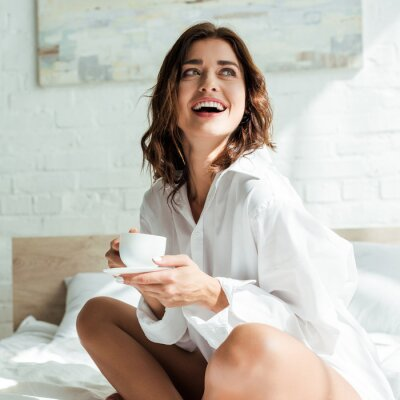 Poster attractive woman in white shirt smiling and holding cup at morning