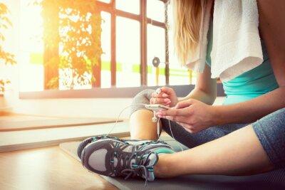 Poster Attraktive blonde Frau mit Smartphone, nachdem Fitness-Workout Ruhe