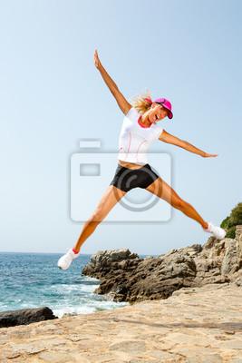 Attraktive Frau in Sportbekleidung Springen im Freien.
