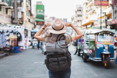 Poster Back view Asian woman tourist backpacker travel in Khao San road, Bangkok, Thailand
