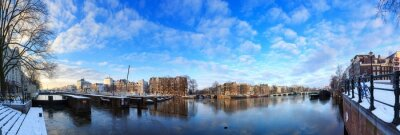 Beautiful 180 degree cityscape panorama of the river Amstel in Amsterdam, the Netherlands, in winter with ice and snow with the famous skinny bridge (magere brug)