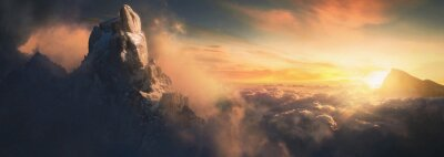 Poster Beautiful aerial landscape of mountain peak at sunset above the clouds - panoramic