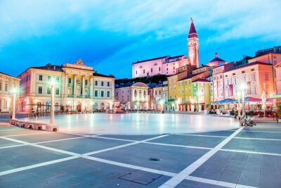 Beautiful amazing city scenery in the central square with the old clock tower in Piran, the tourist center of Slovenia in the light of lanterns. popular tourist attraction. Wonderful exciting places.