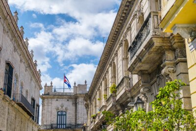 Beautiful ancient building in Havana, Cuba. Cuban flag in the background