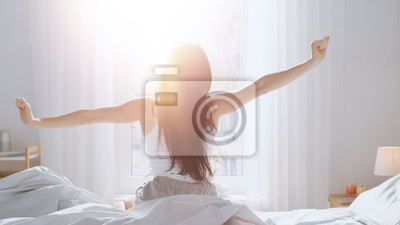 Poster Beautiful Brunette is Waking up in the Morning, Stretches in the Bed, Sun Shines on Her From the Big Window. Happy Young Girl Greets New Day with Warm Sunlight Flare.