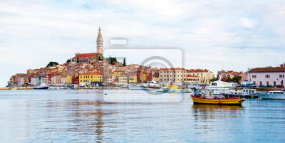 Beautiful city landscape with sea boats, colorful houses and an ancient tower in Rovinj, Croatia. popular tourist attraction. (vacation, rest - concept)