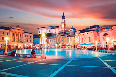 Beautiful city scenery in the central square with the old clock tower in Porec, the tourist center of Croatia, in the light of lanterns.