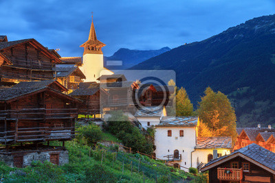 Beautiful cityscape of the alpine village Grimentz, Switzerland, with traditional wooden houses and church tower during the blue hour on a summer night