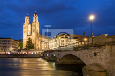 Beautiful cityscape of Zurich, Switzerland, with the Grossmünster Protestant church and the Helmhaus museum, seen from the shore of the river Limmat in the blue hour in summer