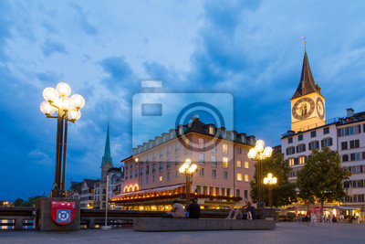 Beautiful cityscape of Zurich, Switzerland, with the St. Peter and Fraumunster churches and people relaxing at the bridge over the river Limmat in the blue hour in summer on July 25, 2014