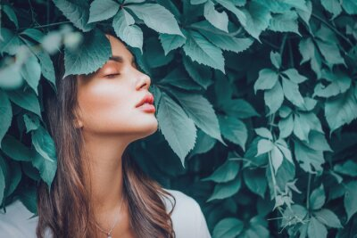 Poster Beautiful fashion model girl enjoying nature, breathing fresh air in summer garden over Green leaves background. Harmony concept. Healthy beauty woman outdoor portrait
