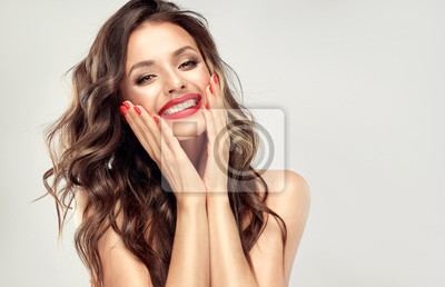 Poster Beautiful laughing brunette model  girl  with long curly  hair . Smiling  woman hairstyle wavy curls . Red  lips and  nails manicure .    Fashion , beauty and make up portrait
