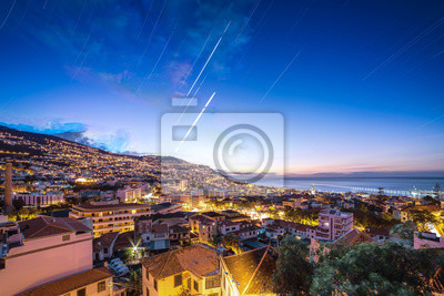 Beautiful long exposure stacked view of the skyline cityscape of the city Funchal on the island Madeira at sunrise in summer with startrails