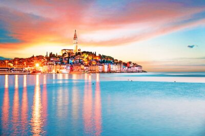 Beautiful  magical city landscape with sea, colorful houses and an ancient tower in Rovinj, Croatia at evening lights at sunset. popular tourist attraction. (vacation, rest - concept)