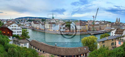 Beautiful panorama of the city of Zurich, Switzerland, at the river Limmat after sunset in the blue hour with the crane and Grossmünster  church on the skyline