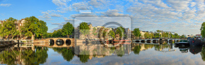 Beautiful panoramic panorama of the river Amstel and the skinny bridge (Magere brug) in Amsterdam, the Netherlands, on a sunny summer morning with some clouds and a mirror reflection