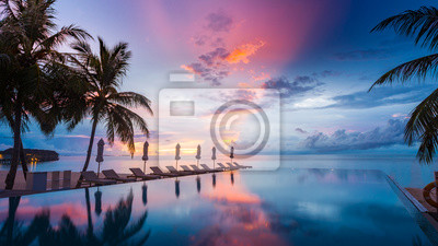 Poster Beautiful poolside and sunset sky. Luxurious tropical beach landscape, deck chairs and loungers and water reflection