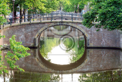 Beautiful summer morning view of the bridges over the famous UNESCO world heritage Reguliersgracht canal in Amsterdam, The Netherlands, with a mirror reflection