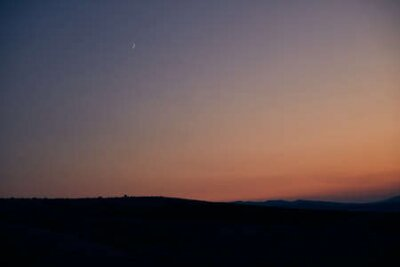 Poster beautiful sunset and new moon on the background of hills
