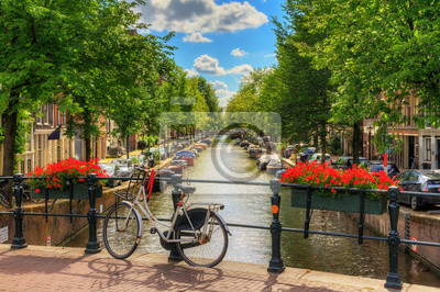 Poster Beautiful vibrant summer flowers and a bicycle on a bridge on the famous world heritage canals of Amsterdam, The Netherlands