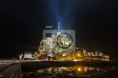 Beautiful view of historic landmark Le Mont Saint-Michel in Normandy, France, a famous UNESCO world heritage site and tourist attraction, at night with reflection