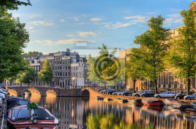 Beautiful view of the iconic UNESCO world heritage Keizersgracht canal  in Amsterdam, the Netherlands, on a sunny summer morning with sunshine, a blue sky and reflection