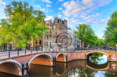 Beautiful view of the iconic UNESCO world heritage Prinsengracht and Reguliersgracht canals in Amsterdam, the Netherlands, on a sunny summer morning with a blue sky and reflection