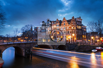 Beautiful view on the Brouwersgracht in Amsterdam, the Netherlands, with a passing canal tour boat after sunset