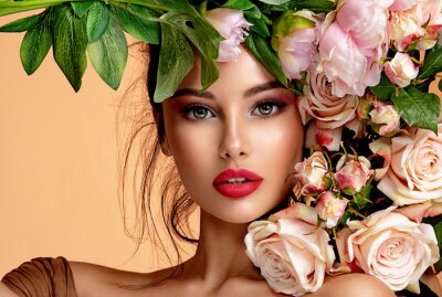 Poster Beautiful white girl with flowers. Stunning brunette girl with big bouquet flowers of roses. Closeup face of young beautiful woman with a healthy clean skin. Pretty woman with bright makeup