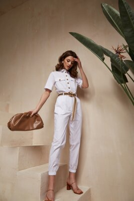 Poster Beautiful woman fashion model brunette hair tanned skin wear white overalls button suit sandals high heels accessory bag clothes style journey safari summer collection plant flowerpot wall stairs.