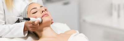 Poster Beautiful woman in professional beauty salon during photo rejuvenation procedure