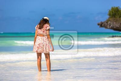 Beautiful woman wearing a hat in a amazing green water beach in Zanzibar in Tanzania