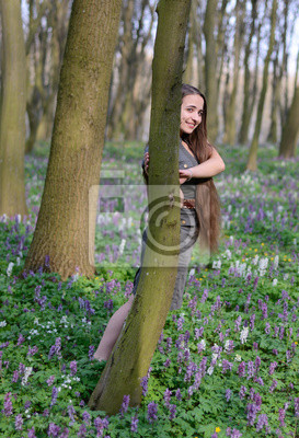 Beautiful young girl on a sunny day in spring forest among flowe