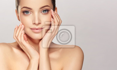 Poster Beautiful young woman with clean fresh skin on face . Girl facial  treatment   . Cosmetology , beauty  and spa .