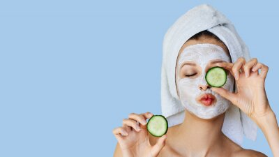 Poster Beautiful young woman with facial mask on her face holding slices of cucumber. Skin care and treatment, spa, natural beauty and cosmetology concept.