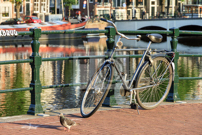 Bicycle on a bridge on the famous world heritage canals of Amsterdam, The Netherlands, on a sunny summer day with a pigeon