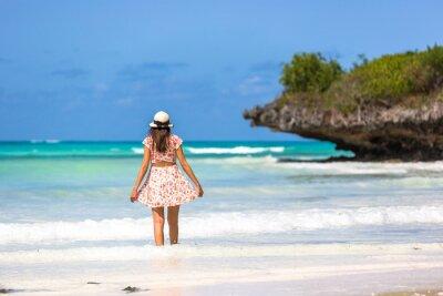 Black hair woman wearing a hat in a amazing blue water beach in Zanzibar in Tanzania